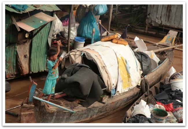 Tämä veneen pikkupoika oli tehnyt itselleen joessa virtaavista roskista leijan. Löydätkö kuvasta?