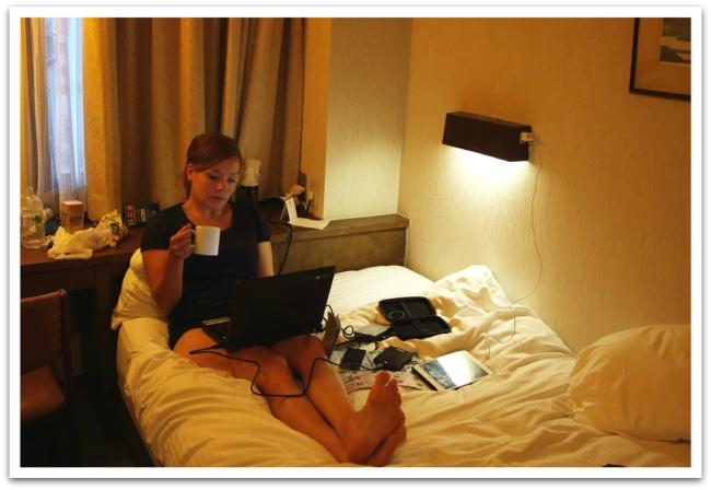 Tätä se reissaus oikeasti on: kaikki mahdolliset elektroniset laitteet sylissä ja kahvikuppi kädessä hotellihuoneen sängyssä.